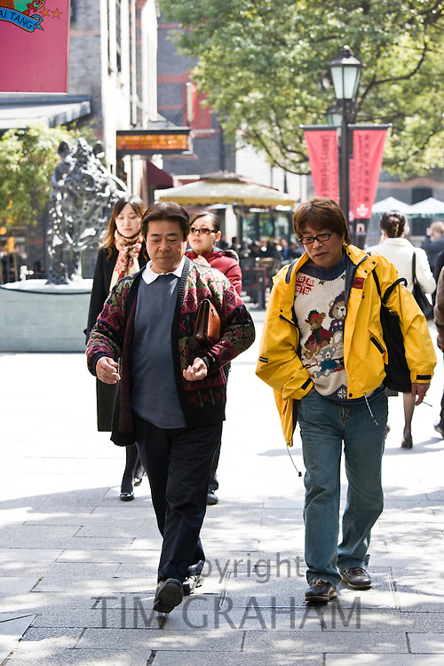 Men walking in redeveloped Xintiandi area, Huang Pi Road, Shanghai, China