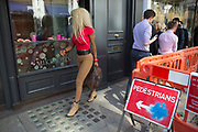 Woman wearing tight fitted clothes checks herself out in a shop window on New Bond Street, London, UK.