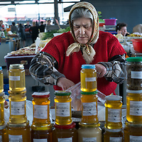 TIMISOARA, ROMANIA - APRIL 21:  A market seller seen at her stall of honey at the daily market on April 21, 2013 in Timisoara, Romania.  Romania has abandoned a target deadline of 2015 to switch to the single European currency and will now submit to the European Commission a programme on progress towards the adoption of the Euro, which for the first time will not have a target date. (Photo by Marco Secchi/Getty Images)