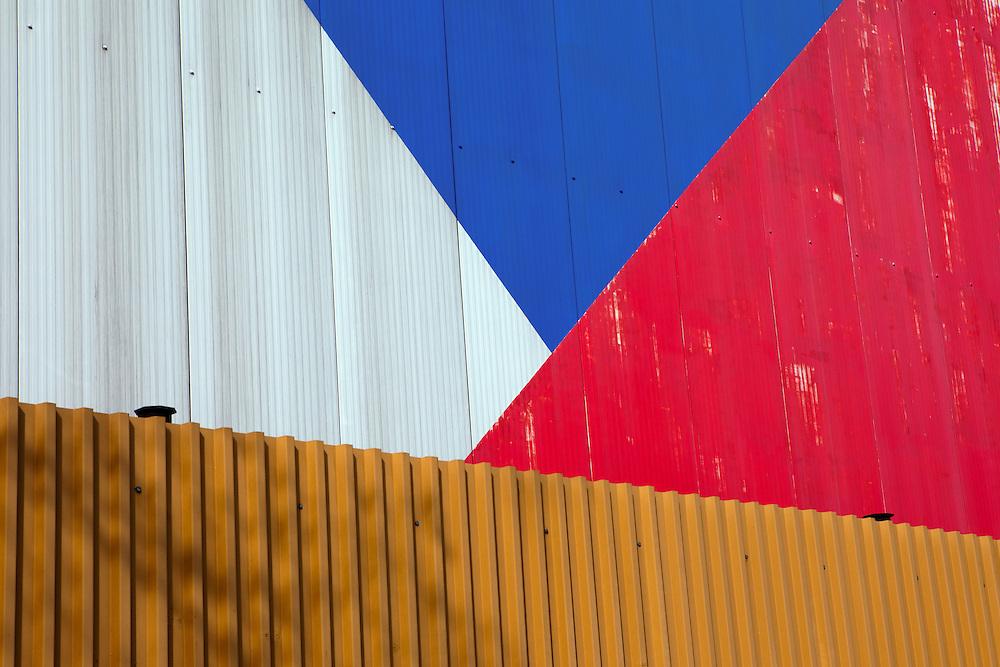 Die tschechische Flagge an einem Fabrikgebaeude in der Stadt Mlada Boleslav wo sich die Skoda Autowerke befinden. Mlada Boleslav liegt noerdlich von Prag und ist ungefaehr 60 Kilometer von der tschechischen Haupstadt entfernt. Skoda Auto beschäftigt in Tschechien 23.976 Mitarbeiter (Stand 2006), den Grossteil davon in der Zentrale in Mlada Boleslav. Damit sind mehr als 3/4 aller Erwerbstätigen der Stadt in dem Automobilkonzern tätig.<br /> <br />                                          Czech flag on a factory building in the city of Mlada Boleslav. The city is located north of Prague and about 60 km away from the Czech capital. Skoda Auto has about 23.976 employees (2006) in Czech Republic and a big part of them is working in Mlada Boleslav. 3/4 of the working population in Mlada Boleslav is working for the Skoda Auto company.