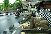 Carving and small shrine at intersection. <br /> Denpasar, Bali
