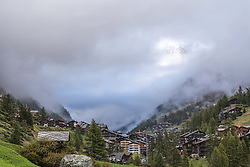 A hole in the clouds over Zermatt Switzerland make a window for the mountains beyond to shine through.