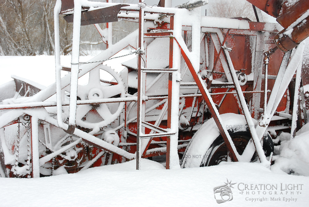 Abandoned in a field near Klamath Falls, Oregon this piece of farming equipment is exposed to the elements and covered in snow.