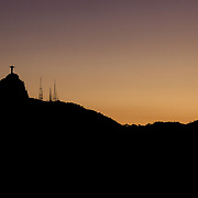 The iconic Cristo Redentor, Christ the Redeemer statue at sunset with communication antenna atop the mountain Corcovado shot from Suger Loaf Mountain. The Christ statue was voted one of the seven wonders of the modern world in 2007. It was designed by Brazilian Heitor de Silva Costa and was inaugurated in 1931 having taken years to assemble. Rio de Janeiro, Brazil. 21st July 2010. Photo Tim Clayton...