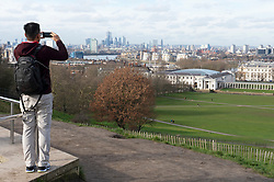 © Licensed to London News Pictures. 12/02/2019. Greenwich, A young man takes a picture of the London landscape on his mobile. Bright and milder weather today in Greenwich Park, South East London . Photo credit: Grant Falvey/LNP