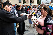 A Roman Catholic priest blesses gathered pets and pet owners during the annual blessing of the animals on the feast day of San Antonio Abad at Oratorio de San Felipe Neri church in the historic center of San Miguel de Allende, Guanajuato, Mexico.