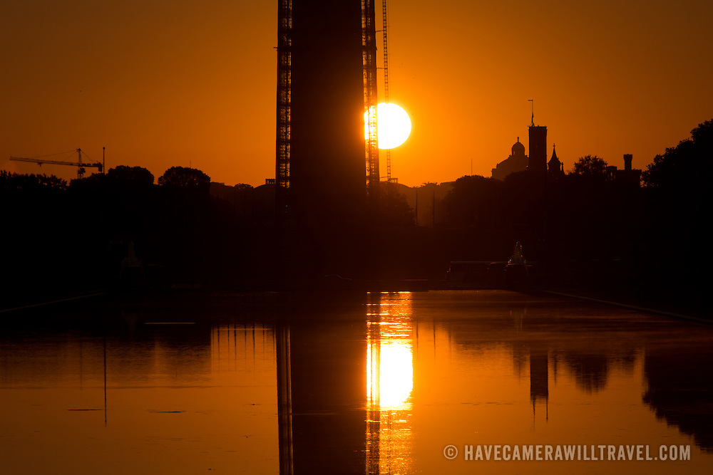 The rising sun very low on the horizon behind the Washington Monument and Reflecting Pool in Washington DC.