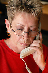 Switchboard operator answering telephone call into busy Hospital call centre,