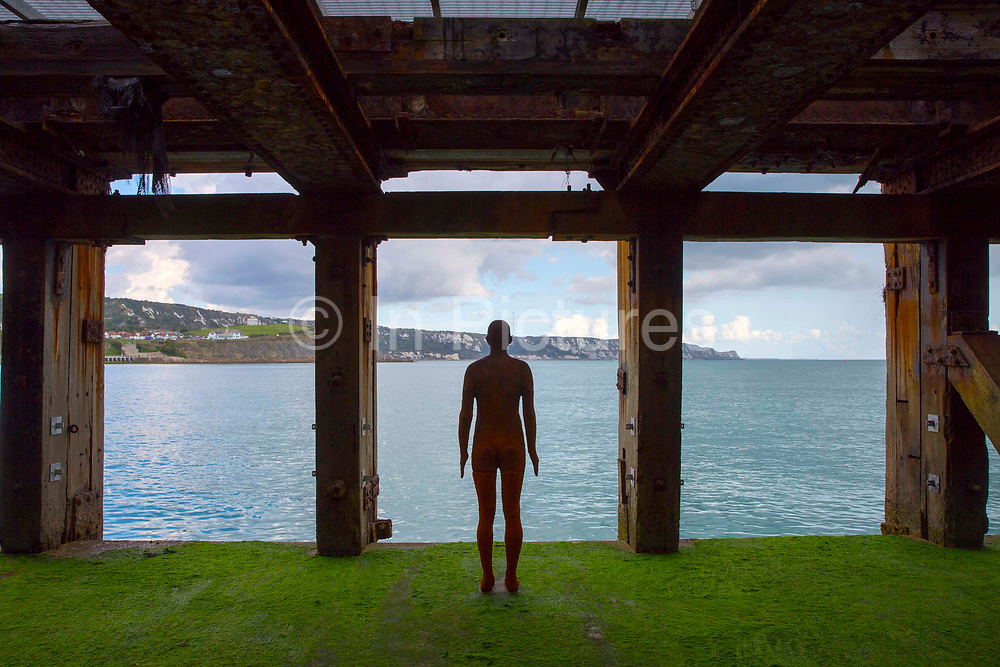 An Antony Gormley cast iron figure from the series 'Another Time' located on the half tide loading bay of the Folkestone Harbour Arm. Part of the 2017 Folkestone Triennial. Folkestone, Kent.