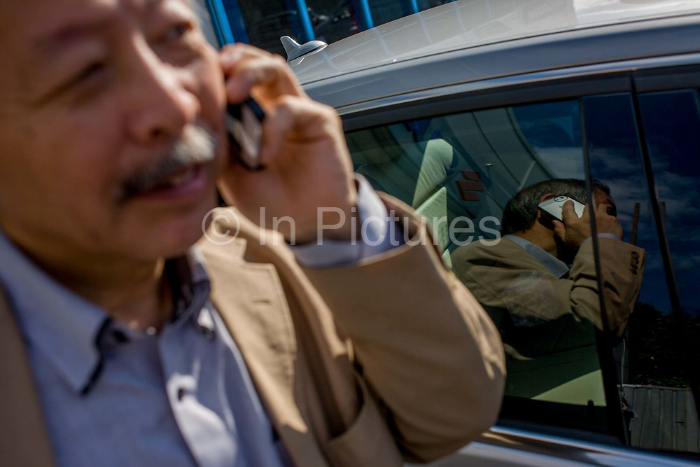 Japanese entrepreneur, Tetsuro Hama makes calls outside his north London car dealership business. Hama is the owner of So plus a north London car dealership. He arrived from Japan in 1973, looking for business opportunities before starting a hotel in a Bayswater backstreet. He then went into the restaurant industry, soon earning the respect of employees and customers for affordable and tasty sushi. From the chapter entitled 'The Price of Happiness' and from the book 'Risk Wise: Nine Everyday Adventures' by Polly Morland (Allianz, The School of Life, Profile Books, 2014).