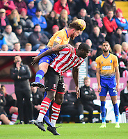 Lincoln City's John Akinde vies for possession with  Mansfield Town's Ryan Sweeney<br />