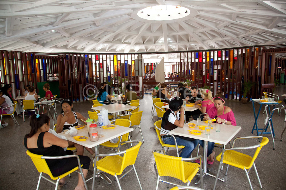 People sitting and eating at Coppelia ice cream parlour, Vedado, Havana new town, a favourite spot for locals and tourists alike, Coppelia is a Havana institution, taking up a whole park.