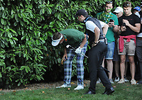 Golf - 2019 BMW PGA Championship - Thursday, First Round<br /> <br /> Ian Poulter of England gets advice from the referee after driving into the bushes, at the West Course, Wentworth Golf Club.<br /> <br /> COLORSPORT/ANDREW COWIE