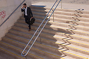 A businessman descends stairs past zigzag shadows of steps at Alameda metro station, Lisbon, Portugal.