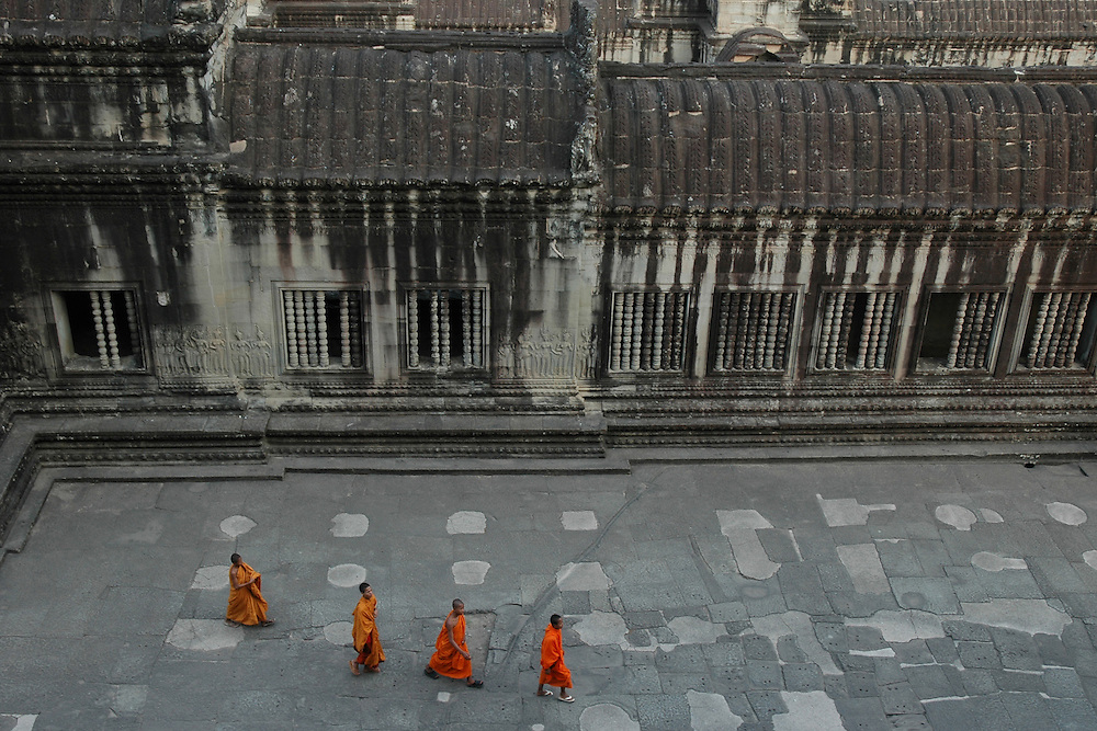 These four Cambodian Buddhist Monks were walking in the interior courtyard of the Angkor Wat temple complex,a massive three-tiered pyramid crowned by five lotus-like towers rising 65 meters from ground level. <br /> <br /> Angkor Wat, the world's largest single religious monument, built for the king Suryavarman II in the early 12th century as his state temple and capital city.  The ruins of Angkor, a UNESCO World Heritage Site with temples numbering over 1000, are hidden amongst forests and farmland to the north of the Tonle Sap Lake outside the modern city of Siem Reap, Cambodia. <br /> <br /> Angkor Wat has remained a significant religious centre since its foundation--first Hindu, dedicated to Vishnu, then Buddhist. Quite a few of the temples at Angkor have been restored and represent a significant site of Khmer architecture.  Angkor Wat has become a symbol of Cambodia, appearing on its national flag and is worthy of all it's attention.