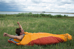 man stretching as he wakes up from sleeping in a sleeping bag in New Mexico