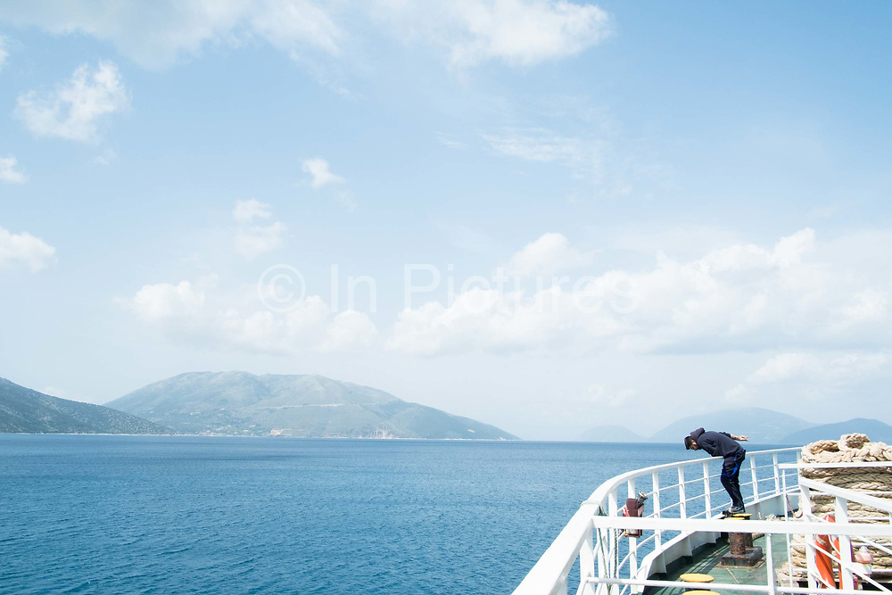 Sailor checking the anchor on leaving port. Sami, Kefalonia, Greece.