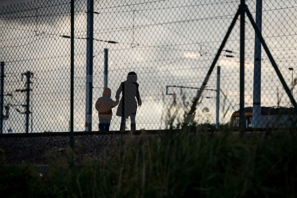 © London News Pictures. Calais, France. A mother and her young daughter cross the tracks at Eurotunnel after climbing underneath a fence. Migrants attempting to reach the UK via the Eurotunnel at Calais in France. The situation has reached crisis point, which French police over run by attempts to cross the border. Photo credit: Ben Cawthra /LNP