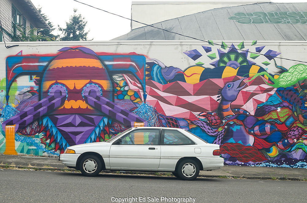 A white car sits in front of a brightly-colored mural of stylized creatures which is painted on the exterior wall of of a building in southeast Portland, Oregon
