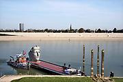 Nederland, Millingen, Nijmegen, 8-4-2020 Vandaag werd een replica van een Romeins masker vervoerd van de scheepswerf in Millingen aan de Rijn naar Het Lentereiland in de nevengeul bij Nijmegen. Het beeld van 6 meter hoog wordt daar geplaatst om als blikvanger en uitkijkpunt te dienen voor de oude stad. Het origineel bevindt zich in museum het Valkhof. De maker en ontwerper is kunstenaar Andreas Hetfeld Foto: Flip Franssen