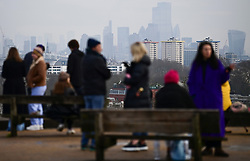 © Licensed to London News Pictures. 15/01/2021. London, UK. The London Skyline can be seen behind members of the public as they gather on Primrose Hill, North London. The Met police has urged Londoners to stick to lockdown rules which were introduced to fight the spread of a new, more aggressive strain of COVID-19. Photo credit: Ben Cawthra/LNP