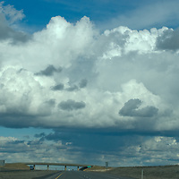 WASHINGTON.  Winter storm clouds tower above coulee country west of Spokane.  Interstate 90 foreground.