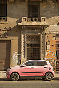 Side view of pink car parked on street in front of derelict building, Casablanca, Morocco.