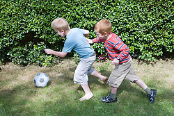 Two brothers playing football in the garden,