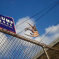 PHILADELPHIA, PA - OCTOBER 19:  A tattered flag waves beside a Donald Trump campaign sign in the background of a residence in Philadelphia, PA October 19, 2016.