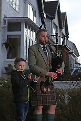Finlay MacDonald plays the pipes at his home in Glasgow alongside sons Elliott, ten, and Fionn, eight to salute local heroes during Thursday's nationwide Clap for Carers NHS initiative to applaud NHS workers fighting the coronavirus pandemic.