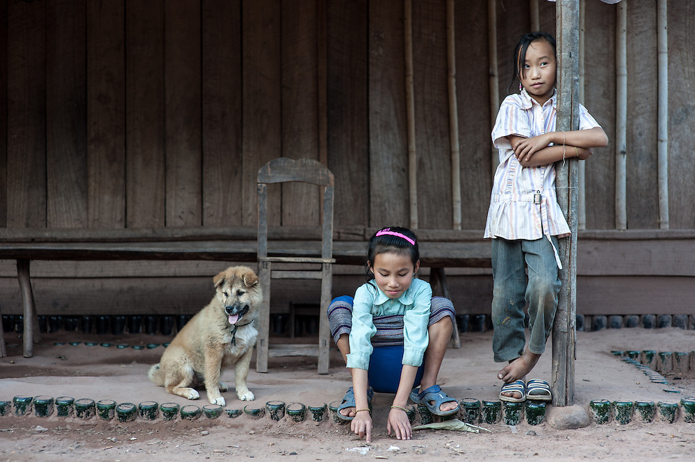 Girls hang out in front of a home in Naten Village in Phongsali Province