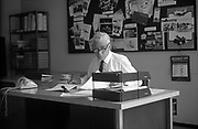 A middle-aged businessman looks up from paperwork during a working day in his 1970s Brussels office. The executive wearing a white shirt and tie pauses writing with a pencil to look over his glasses, past the In Tray and towards the viewer. There is no computer or electronic devices that describe this decade towards the end of the 20th century. The calendar shows us today's date of July 5th 1971. The picture shows us a memory of nostalgia in an era from the last century.