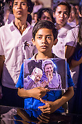 """04 FEBRUARY 2013 - PHNOM PENH, CAMBODIA:  A Cambodian boy holds a portrait of King-Father Norodom Sihanouk during the King-Father's cremation service in Phnom Penh. Norodom Sihanouk (31 October 1922- 15 October 2012) was the King of Cambodia from 1941 to 1955 and again from 1993 to 2004. He was the effective ruler of Cambodia from 1953 to 1970. After his second abdication in 2004, he was given the honorific of """"The King-Father of Cambodia."""" Sihanouk died in Beijing, China, where he was receiving medical care, on Oct. 15, 2012.   PHOTO BY JACK KURTZ"""