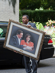 © Licensed to London News Pictures. LONDON, UK  01/07/11. An aid to the President of Pakistan, Asif Ali Zardari, carries a portrait of British Prime Minister David Cameron and his wife Samantha as the president arrives at 10 Downing Street for talks. Discussions between Mr Cameron and Mr Zadari are expected to discuss allied troop withdrawals from Afghanistan and security on the Afghanistan/Pakistan border.  Please see special instructions for usage rates. Photo credit should read Matt Cetti-Roberts/LNP
