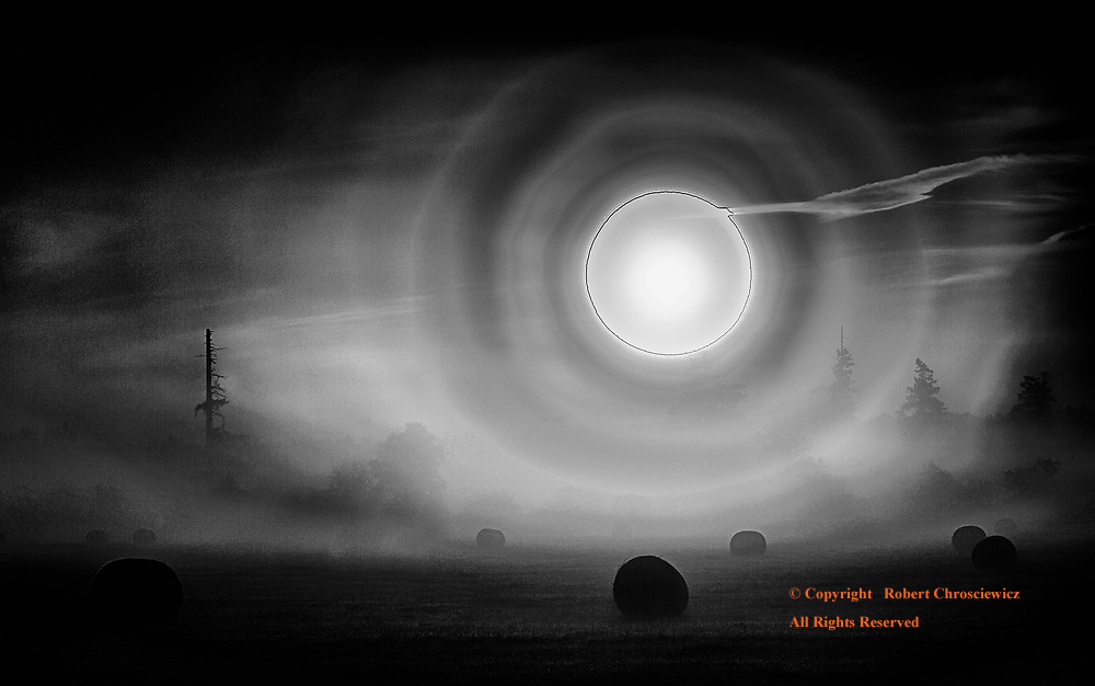 Surrealistic Fog (B&W):  The sun displays as a ball of fire and dominates this surrealistic scene, as it attempts to break through the thick morning fog that engulfs a newly harvested hay field, Surrey British Columbia Canada.