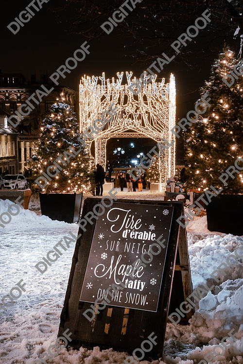 Montreal, Quebec, Canada - January 3, 2021 A sign offering Maple taffy on the snow in the place Jacques-Cartier in Old Montreal with Christmas lights and winter decorations in the background