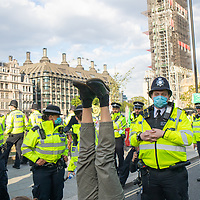 During Extinction Rebellion protests for action on climate change, a protestor does some yoga in front of a Police cordon.