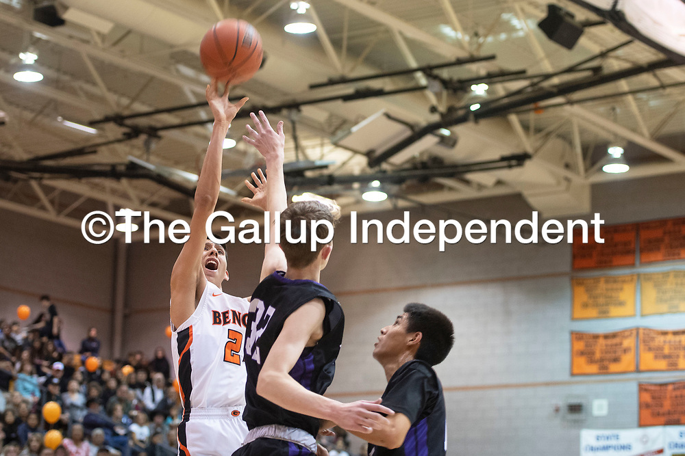 Gallup Bengal Quinn Atazhoon (24) takes a jump shot as Miyamura Patriot Christopher Mortensen (32) defends Wednesday night at Gallup High School in Gallup. Gallup took the win 56-51.