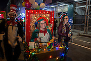 """New York, NY - 31 October 2015. A woman dressed as an elf in Santa's workshop, complete with workbench, tools and toys, at the start of the annual Greenwich Village Halloween Parade. Her name tag reads """"Sparkle Twinklebaum."""""""