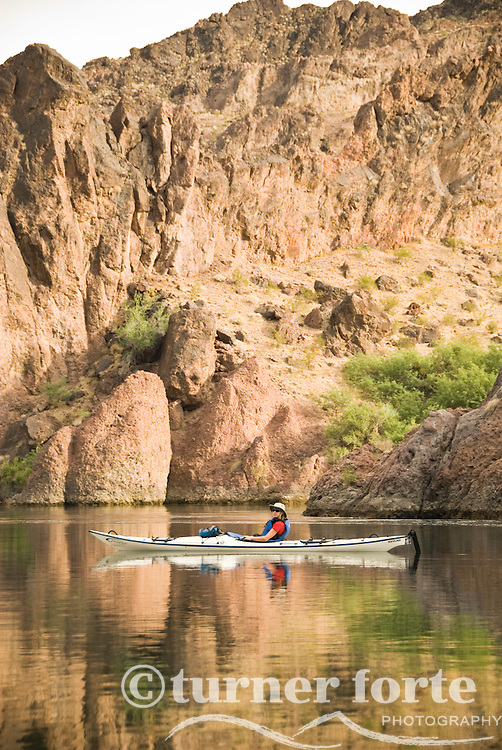 A kayaker paddles through the reflections of The Black Canyon, Nevada.