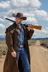 cowboy in a duster carrying a rifle outdoors
