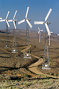 Wind farm producing electricity at Tehachapi Pass, southern California. Wind Turbines. View of a wind farm with several wind turbines each with 3 spinning rotor blades. Wind power is used to drive a turbine for the generation of electricity. The electrical energy produced from a turbine is proportional to the cube of the wind speed. Thus, a 10-meter per second wind will produce 8 times more energy than a 5 meter per second wind. Wind turbines vary in size from large generators with a 1-3 megawatt capacity to small machines producing only a few kilowatts. (1989).