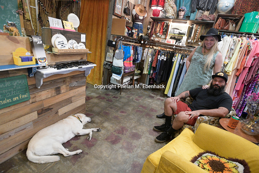 Brittany and Agustin Sulser, owners of The Owl's Attic vintage store, pose with their dog, Dallas, in the Audubon Park neighborhood Saturday, Sept. 23, 2017, in Orlando, Fla. (Photo by Phelan M. Ebenhack)