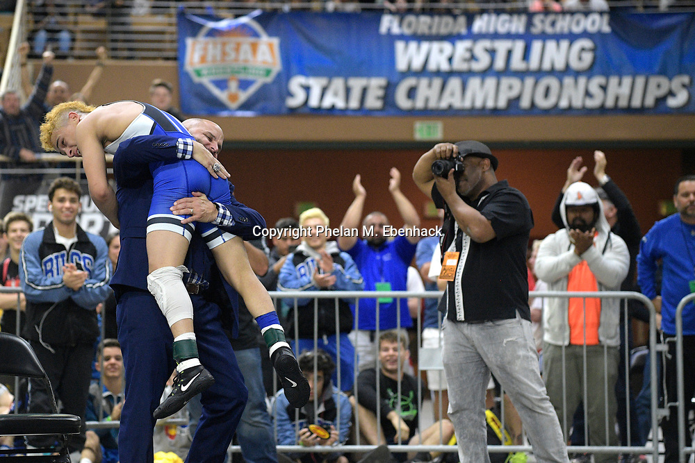 South Dade's Elijah Varona is held by coach Victor Balmaceda after winning his championship match in the 113-lb. Class 3A division during the FHSAA State Wrestling Finals, Saturday, March 4, 2017, in Kissimmee, Fla. (Photo by Phelan M. Ebenhack)
