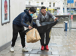 © Licensed to London News Pictures; 03/05/2021; Bristol, UK. Two men try to turn an inverted umbrella the right way during wet and windy weather in Bristol's Broadmead shopping centre for a washout on the early May bank holiday. Photo credit: Simon Chapman/LNP.