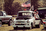 Retro America - 1970's life showing people hanging out in field with trucks. Montville, NJ