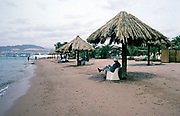 Tourists sitting in shade on sandy beach on Red Sea coast, Aqaba. Jordan, 1998