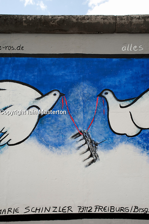 Painting of 2 doves carrying Brandenburg Gate on repainted Berlin Wall at East Side Gallery in Berlin 2009