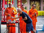 18 SEPTEMBER 2017 - BANGKOK, THAILAND: Buddhist monks chant while a man prays at Wat Mangkon Kamalawat, a Chinese Mahayana temple in Bangkok on the last day Hungry Ghost Month. The Ghost Festival, also known as the Hungry Ghost Festival, Zhongyuan Festival or Yulan Festival is a traditional Buddhist and Taoist festival held in Asian countries. According to the Chinese calendar (a lunisolar calendar), the Ghost Festival is on the 15th night of the seventh month. In Chinese culture, the fifteenth day of the seventh month in the lunar calendar is called Ghost Day and the seventh month in general is regarded as the Ghost Month, in which ghosts and spirits, including those of the deceased ancestors, come out from the lower realm. Distinct from both the Qingming Festival (in spring) and Double Ninth Festival (in autumn) in which living descendants pay homage to their deceased ancestors, during Ghost Festival, the deceased are believed to visit the living.     PHOTO BY JACK KURTZ
