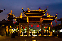 Arch and pagoda illuminated at night in the water town of Zhouzhuang, China